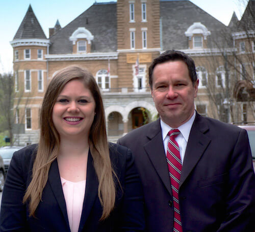 Fayetteville Arkansas lawyers, Grace Casteel and John Hudson, headshot in downtown Fayetteville
